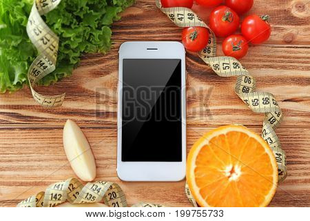 Mobile phone, healthy fresh food and measuring tape on wooden table. Weight loss concept