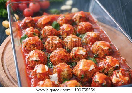 Delicious turkey meatballs in glass casserole dish on wooden board