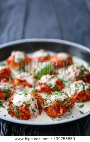 Frying pan with delicious turkey meatballs and sauce on wooden table