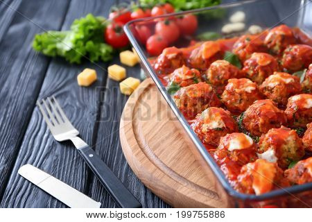 Delicious turkey meatballs in glass casserole dish on wooden table