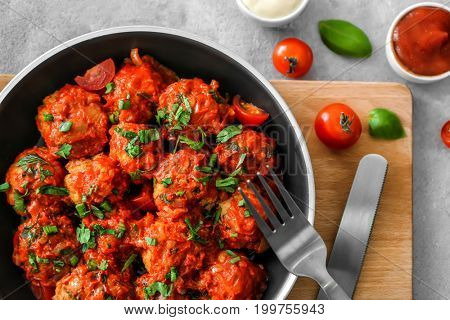 Frying pan with turkey meatballs and tomato sauce on table