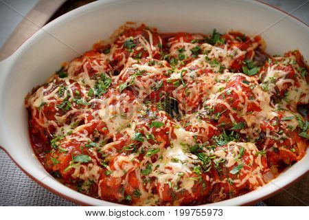 Closeup view of ceramic casserole dish with turkey meatballs, tomato sauce and melted cheese