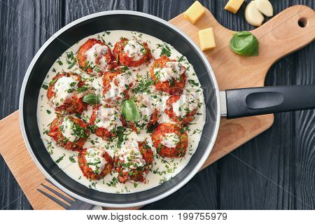 Frying pan with delicious turkey meatballs and sauce on table