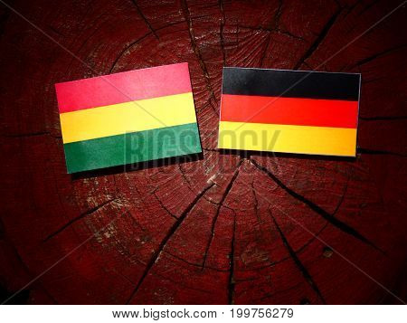 Bolivian Flag With German Flag On A Tree Stump Isolated