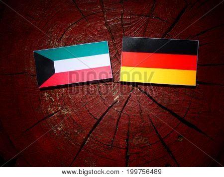 Kuwaiti Flag With German Flag On A Tree Stump Isolated