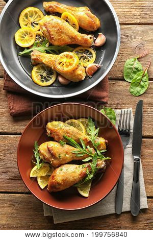 Plate and frying pan with delicious roasted chicken drumsticks on wooden table
