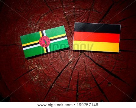 Dominica Flag With German Flag On A Tree Stump Isolated