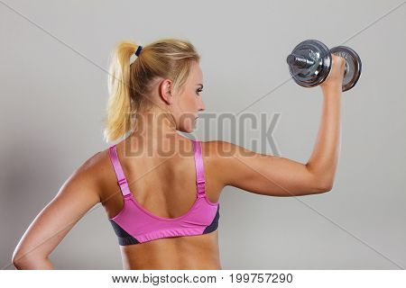 Strong woman lifting dumbbells weights. Fit girl exercising gaining building muscles. Fitness and bodybuilding back view