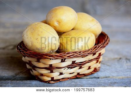 New potatoes. Whole new potato in a wicker basket isolated on a vintage wooden table. Closeup