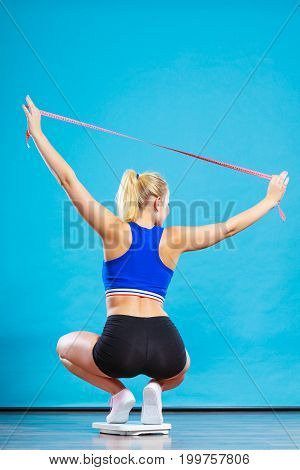 Slimming diet weight loss. Joyful female standing on bathroom scales arms up holds measure tape celebrating success on blue