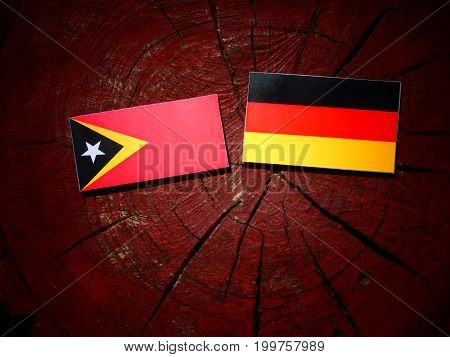 East Timorese Flag With German Flag On A Tree Stump Isolated