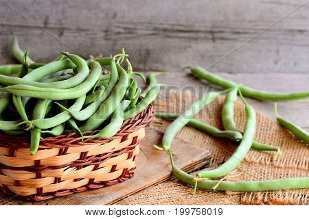 Long green beans in a brown wicker basket on a wooden board and a burlap textile. Vintage wooden background