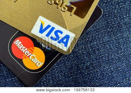 Moscow, Russia - August 05, 2017: Visa and Mastercard credit cards over blue jeans