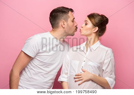 The funny man kissing his beautiful pregnant wife at pink studio background
