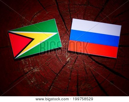 Guyana Flag With Russian Flag On A Tree Stump Isolated