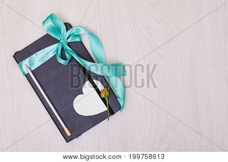 Gift notepad with ribbon on the table. Pencil and sketchbook.