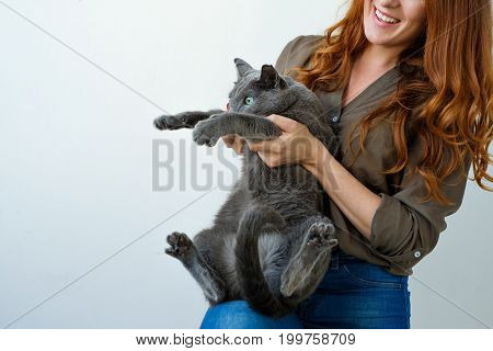 Pretty woman holding her russian blue cat in hands. Cat is afraid of something and looks aside