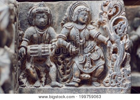 Indian architecture background on traditional style relief with drummer musician and dancing woman inside the 12th century Hoysaleshwara temple in Halebidu, India