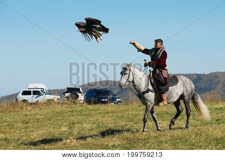 CIRCA ALMATY, KAZAKHSTAN - SEPTEMBER 18, 2011: Unidentified Kazakh man on horse hunts with golden eagle circa Almaty, Kazakhstan.