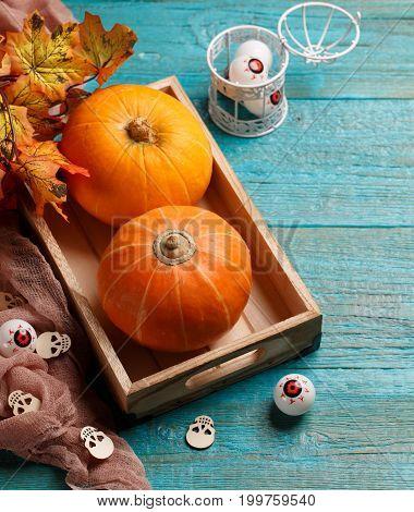 Halloween pumpkins, wooden skulls, , eyeballs on wooden table