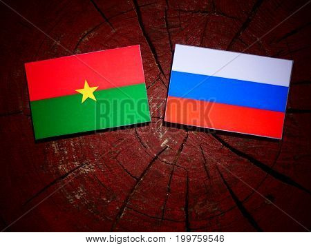 Burkina Faso Flag With Russian Flag On A Tree Stump Isolated