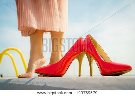 Fashion and footwear. Red high heel classic shoes outdoor during sunny day.