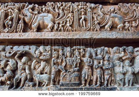 Ornate bas relief with historical Indian background Lord Vishnu sitting Krishna and humans in stone. 12th century Hoysaleshwara temple in Halebidu, India