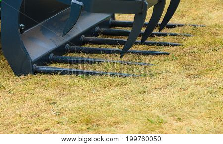 Agricultural harvesting industrial equipment concept. Agriculture machinery. Closeup of cutting scissor hay forklift