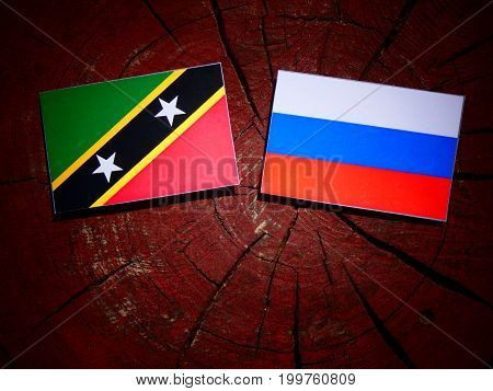 Saint Kitts And Nevis Flag With Russian Flag On A Tree Stump Isolated