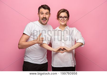 The funny handsome man and his beautiful pregnant wife's tummy at pink studio background