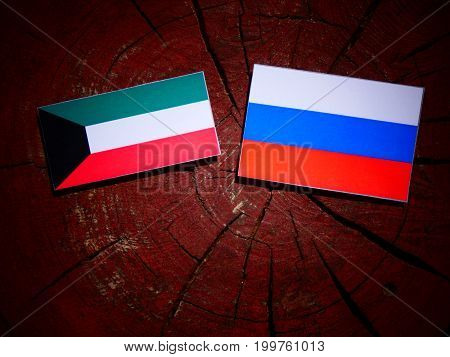 Kuwaiti Flag With Russian Flag On A Tree Stump Isolated