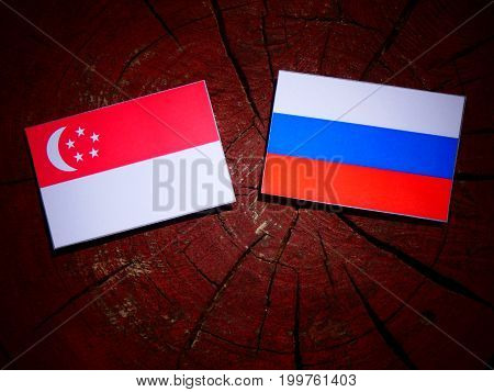 Singaporean Flag With Russian Flag On A Tree Stump Isolated