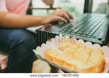 young women eating sweet fat unhealthy food when working with computer laptop