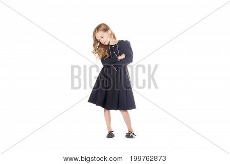 Charming Little Girl In A Black Dress With His Hands Crossed On His Chest. Isolated On White Backgro
