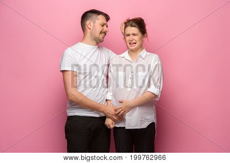 The funny handsome man and his beautiful pregnant wife's tummy at pink studio background. quarrel concept