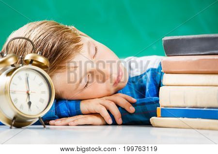 Small boy in shirt sleeping with alarm clock near blackboard. Little student sleeping tired with books after school lessons