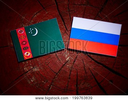 Turkmenistan Flag With Russian Flag On A Tree Stump Isolated