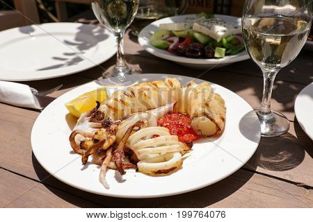 Grilled fresh squid dish as an appetizer on a table served for two in the tavern, also on the table white wine and greek salad. Horizontal. Daylight.
