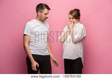 The funny handsome man and his beautiful pregnant wife at pink studio background eating together