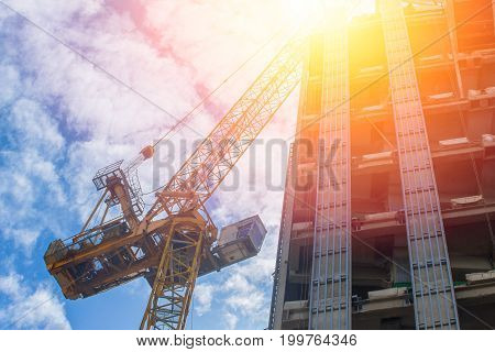 Future of Property asset development industry concept. Crain with under construction building.