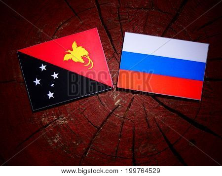 Papua New Guinea Flag With Russian Flag On A Tree Stump Isolated