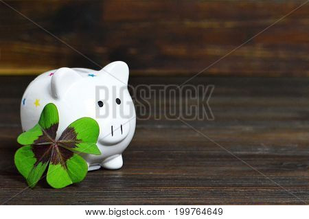 Piggy bank and lucky clover on wooden background