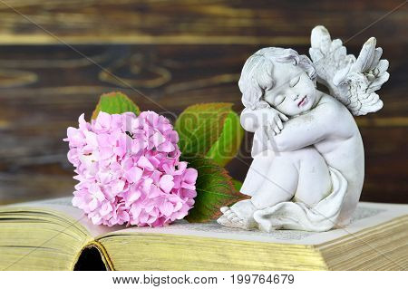 Close up of guardian angel figurine and flower