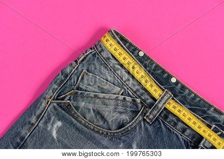 Close up of jeans belt loops and pocket. Healthy lifestyle and dieting concept. Jeans with yellow measure tape instead of belt. Top part of denim trousers isolated on pink background.
