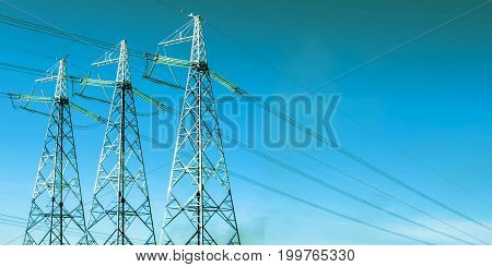 The electric transmission line on background of blue sky