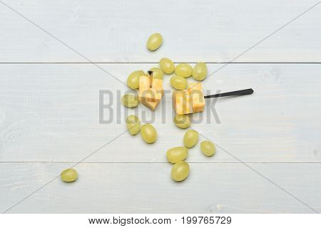 Several White Grapes And Cheese On Vintage Background