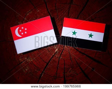 Singaporean Flag With Syrian Flag On A Tree Stump Isolated
