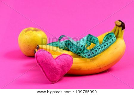 Composition Of Bananas, Apple, Greenish Blue Measuring Tape And Heart