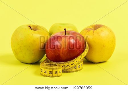 Tape For Measuring And Four Apples, Isolated On Yellow Background