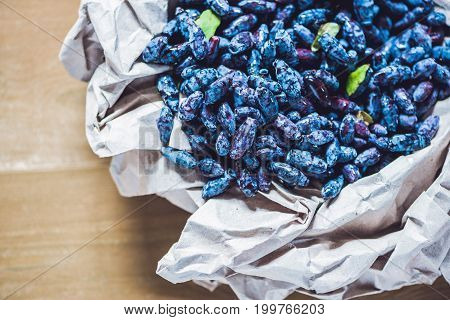 Fresh Honeysuckle Blue Berry Fruits With Leaf On A Wooden Background